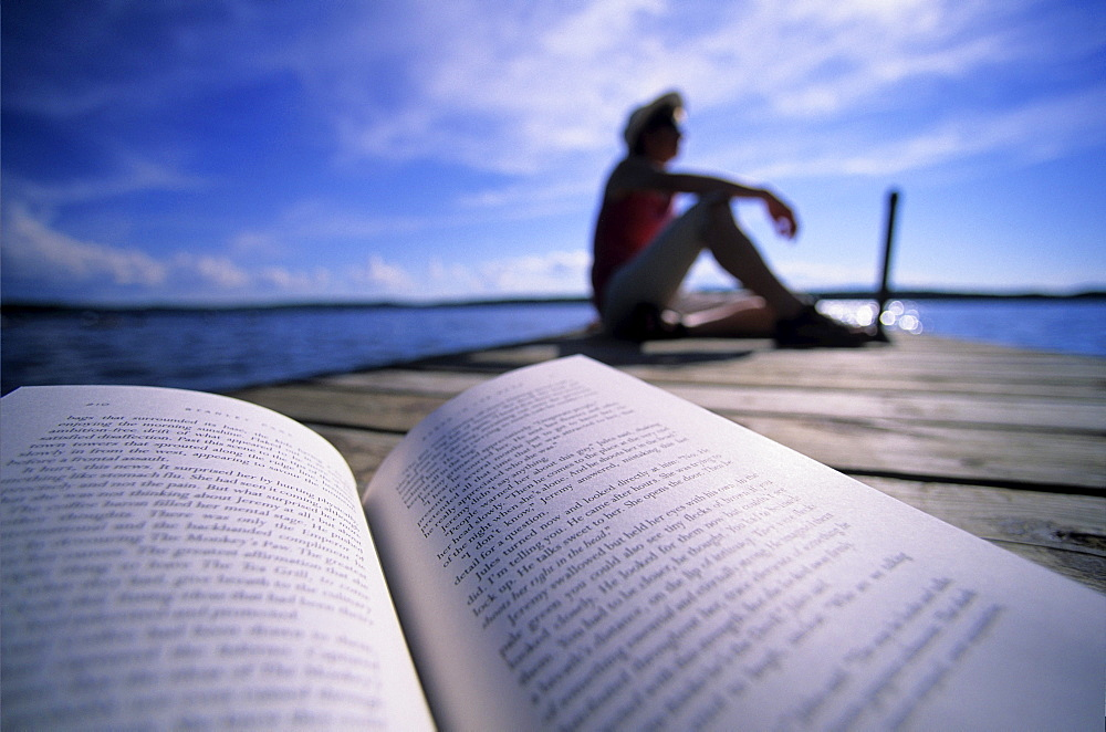 Woman Relaxing on Dock with a Novel.