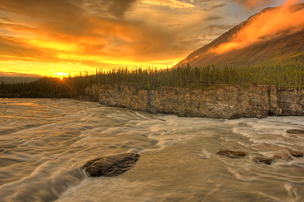 Orange sunset on Sluice Box Rapids above Virginia Falls, Nahanni National Park, Northwest Territories