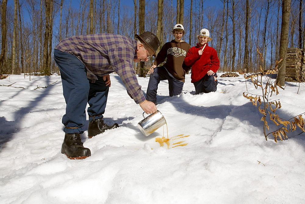 Teenagers Watching Man make Maple Taffy on Snow, St Mathieu du Lac, La Mauricie County, Quebec