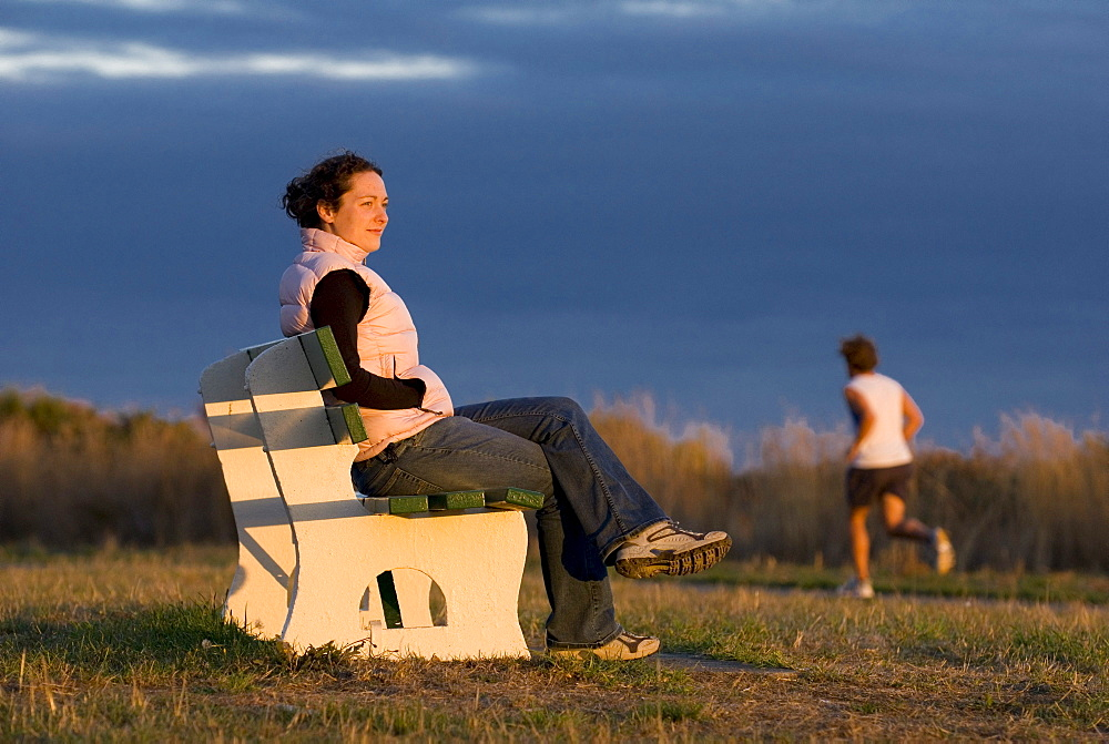 Woman Sitting on Bench at Sunset, Victoria, BC