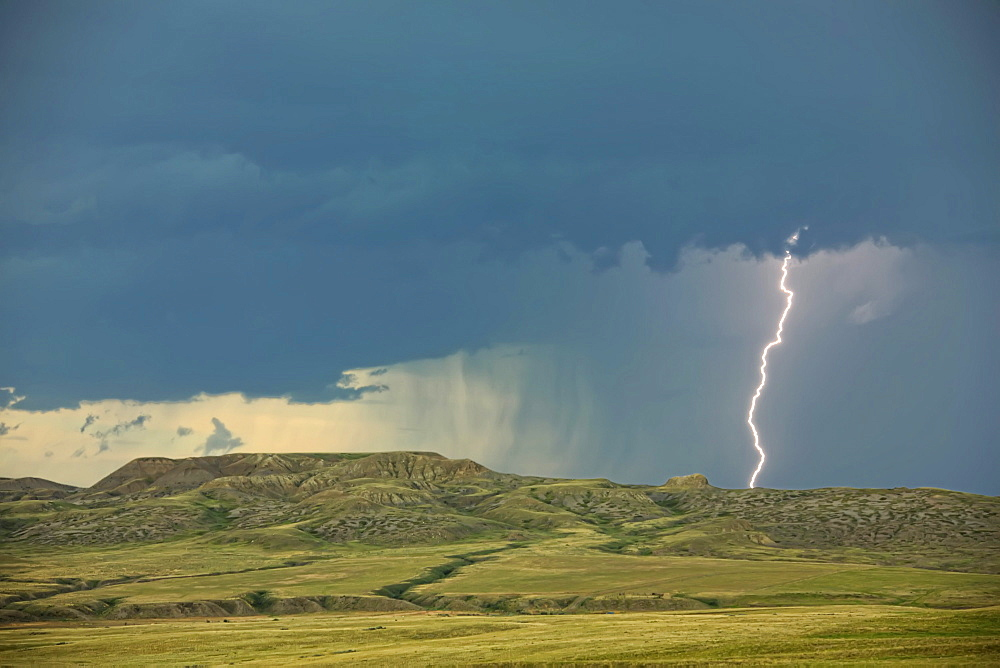Digitally enhanced image with painterly effect of lightning striking over 70 Mile Butte and Sleeping Lion Butte, Grasslands National Park, Saskatchewan