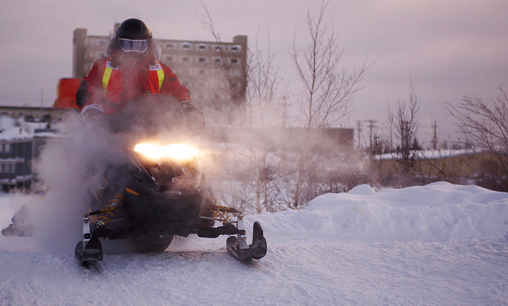Snowmobiler cresting a small hill to come on to Frame Lake in downtown Yellowknife. Photographed at the Rock/Ice Ultra marathon in Yellowknife, Northwest Territories