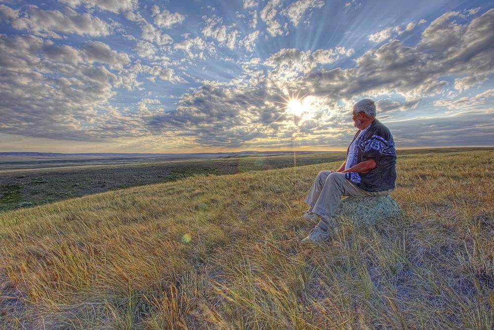 Older gentleman sitting on rock watching sunset on the prairies, Grasslands National Park, Saskatchewan