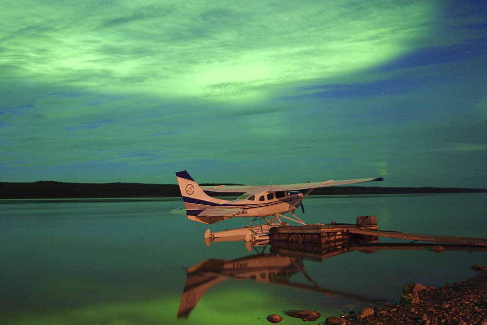 Aurora borealis or northern lights over float plane and Mackenzie River, Fort Simpson, Northwest Territories