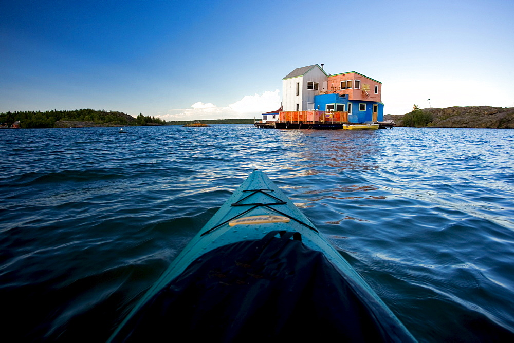Kayaker approaching colourful houseboats, Yellowknife Bay on the Great Slave Lake, Yellowknife, Northwest Territories