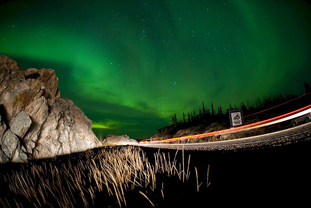 Lights of a passing vehicles under Aurora Borealis at the start of the Ingraham Trail, outside Yellowknife, Northwest Territories