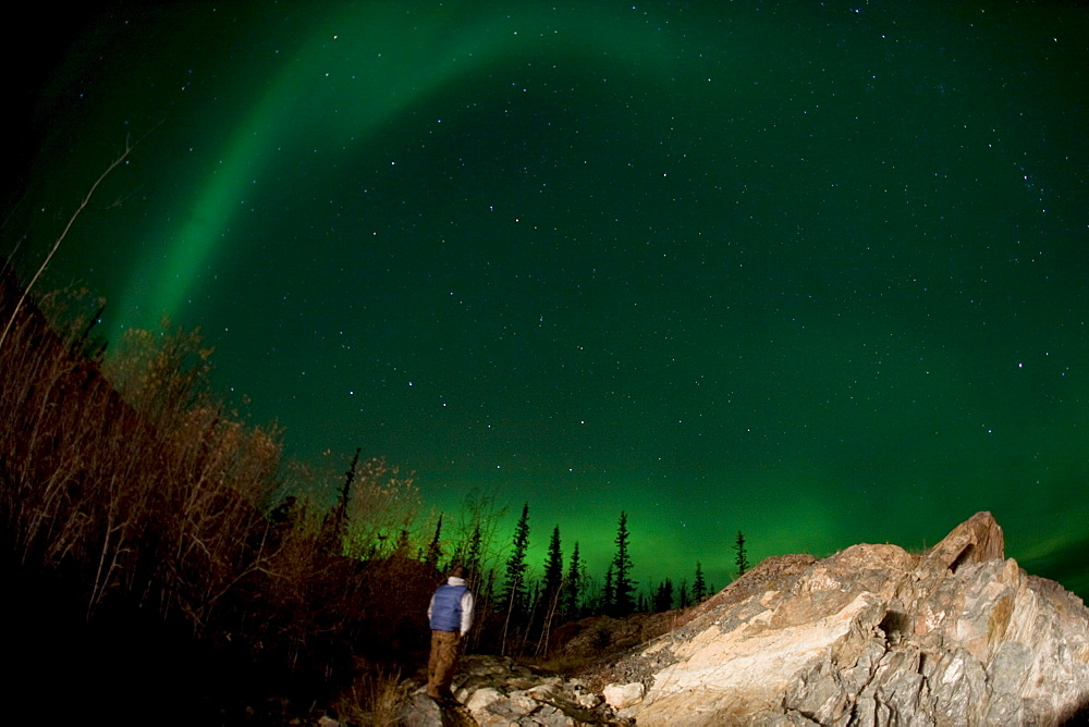 Hiker standing below Aurora Borealis, outside Yellowknife, Northwest Territories