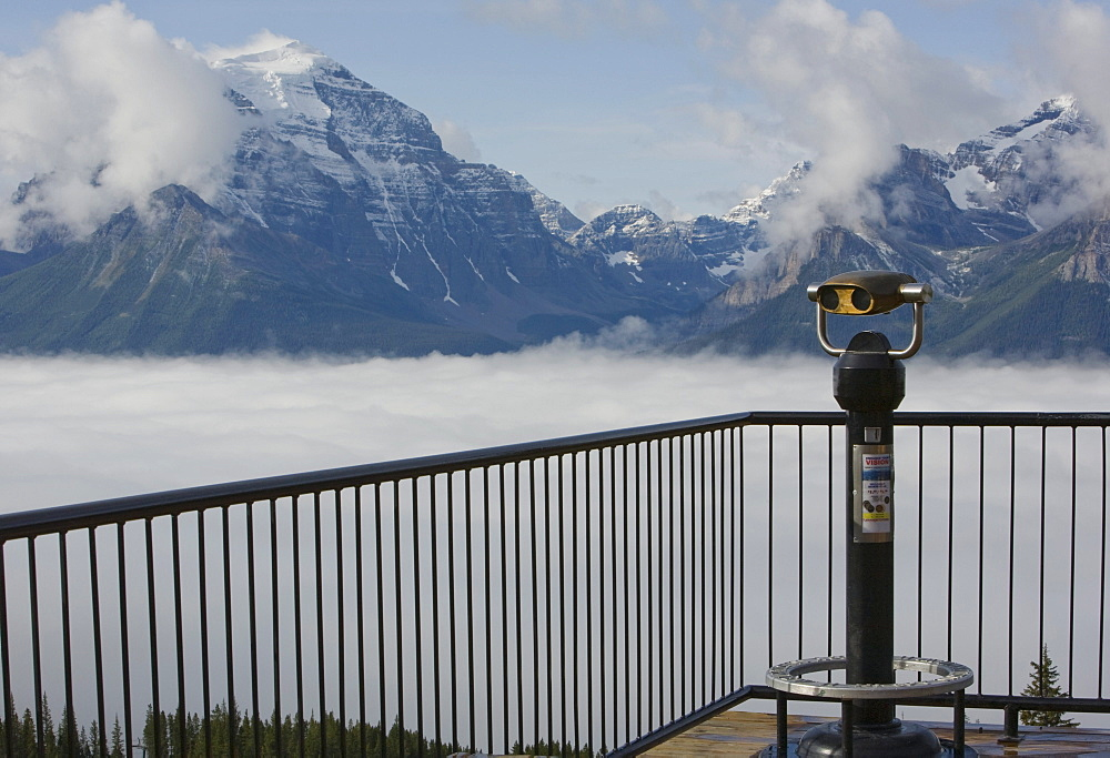 Binoculars on a deck overlooking the Rocky Mountains through the clouds, Lake Louise, Alberta
