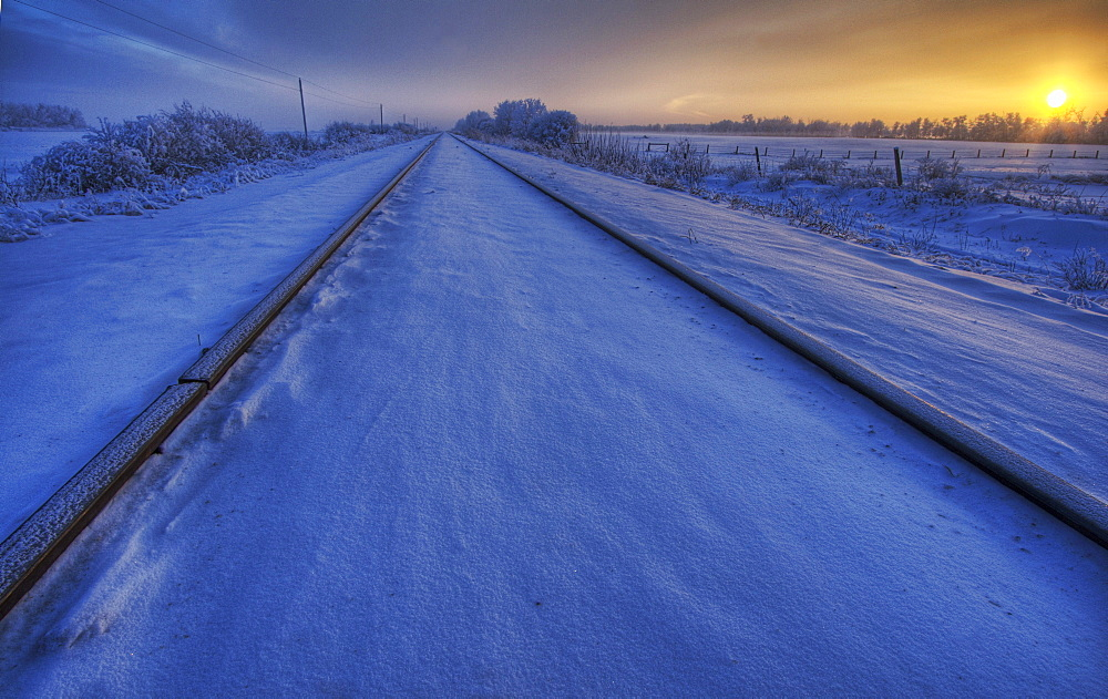 Snow and frost covered railroad tracks at sunset on the Alberta prairies