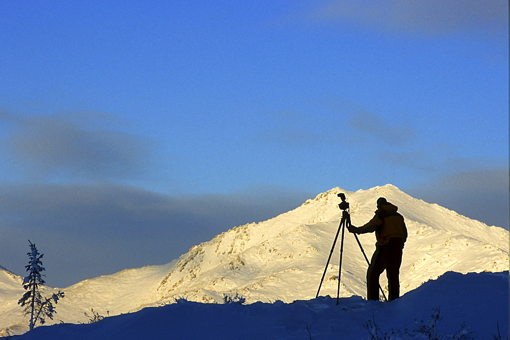 Photographer Silhouetted against the Ogilvie Mountains near the Dempster Highway, Tombstone Territorial Park, Dawson City, Yukon