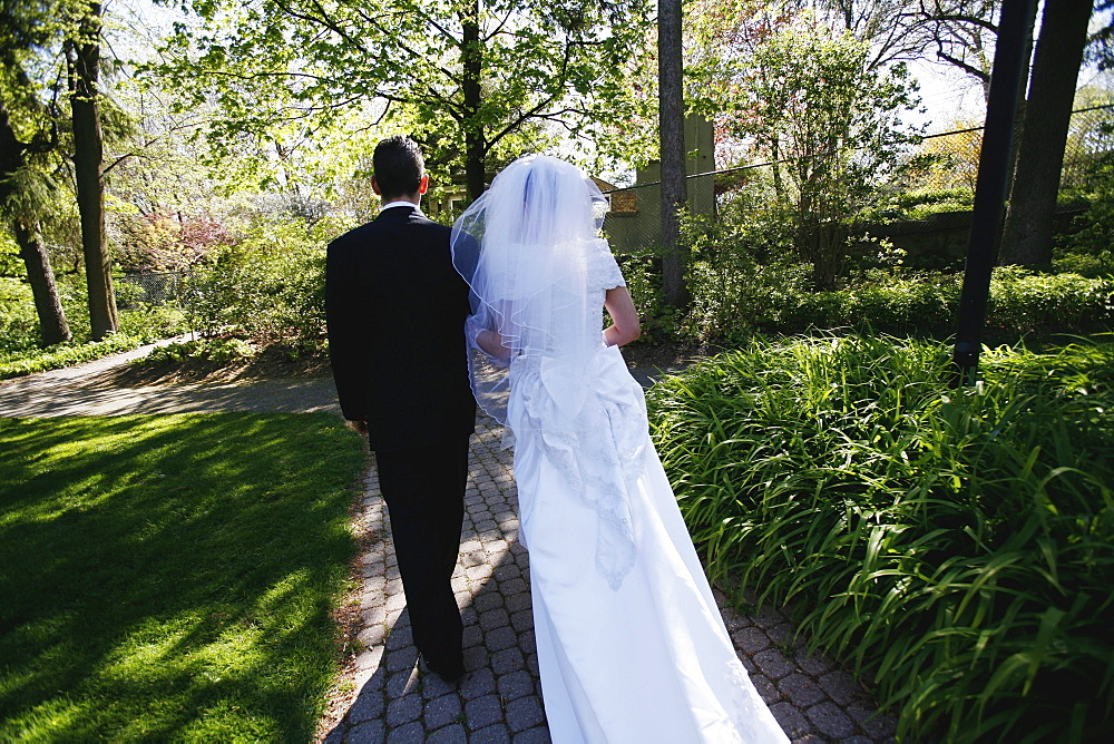 Couple on their Wedding Day Walking down a Path in a Park