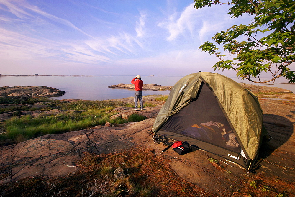Man Looking through Binoculars beside a Tent, Georgian Bay, Killarney, Ontario