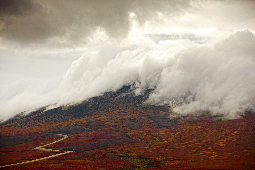 Storm clouds over the Demspter Highway winding its way through the tundra near the Yukon, Northwest Territories border