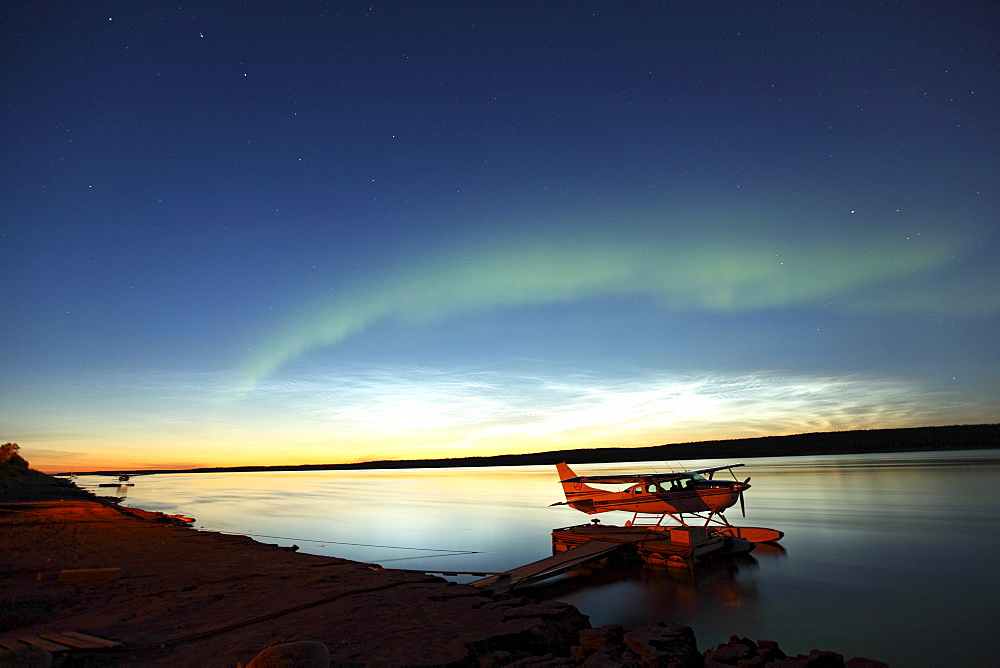 Aurora borealis over the MacKenzie River with float planes in foreground, Fort Simpson, Northwest Territories