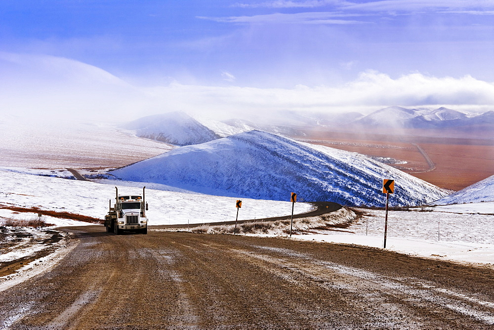 Truck driving on Dempster Highway and fog over Richardson Mountains, Yukon
