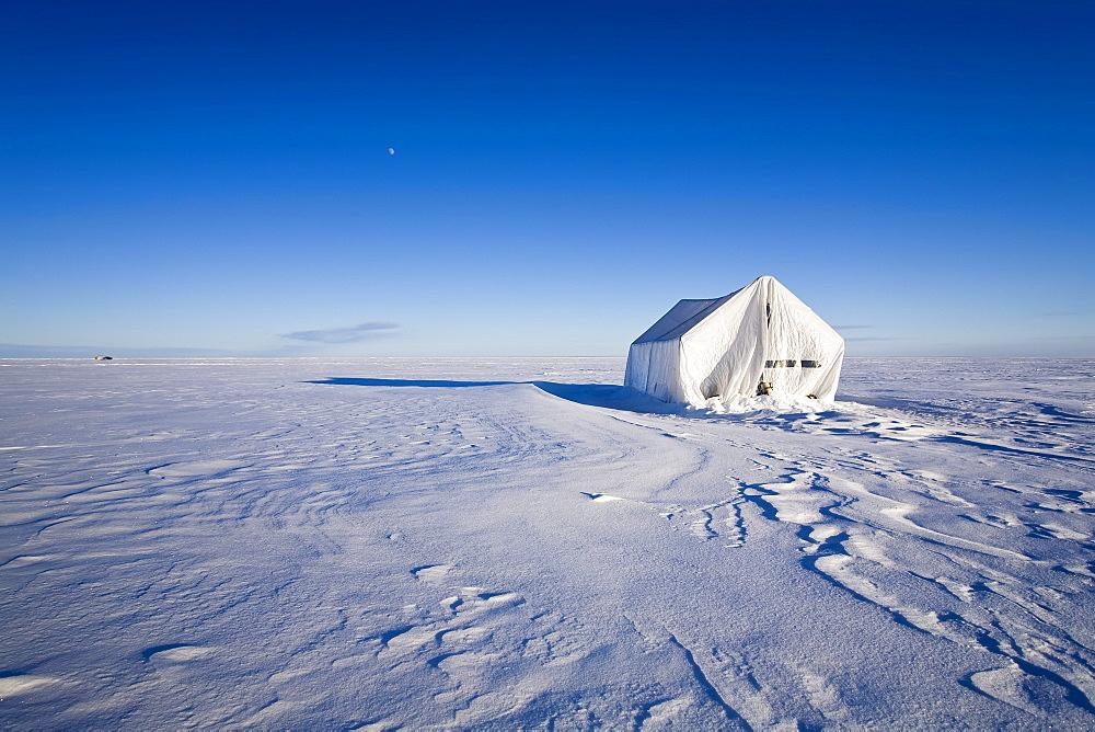 Ice fishing tent at sunset on frozen Lake Winnipeg, near Gimli, Manitoba