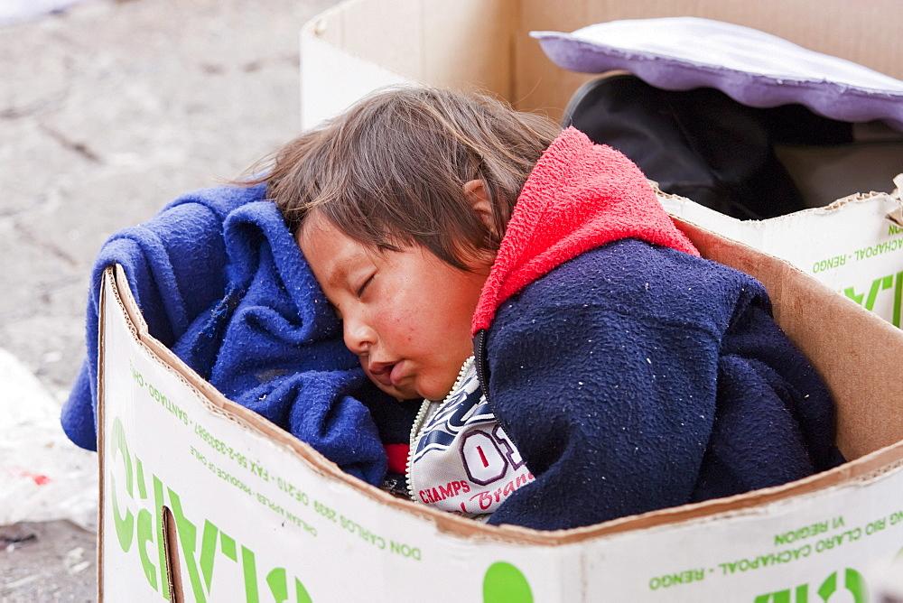 Girl sleeping in a cardboard box, Otavalo, Imbabura, Ecuador