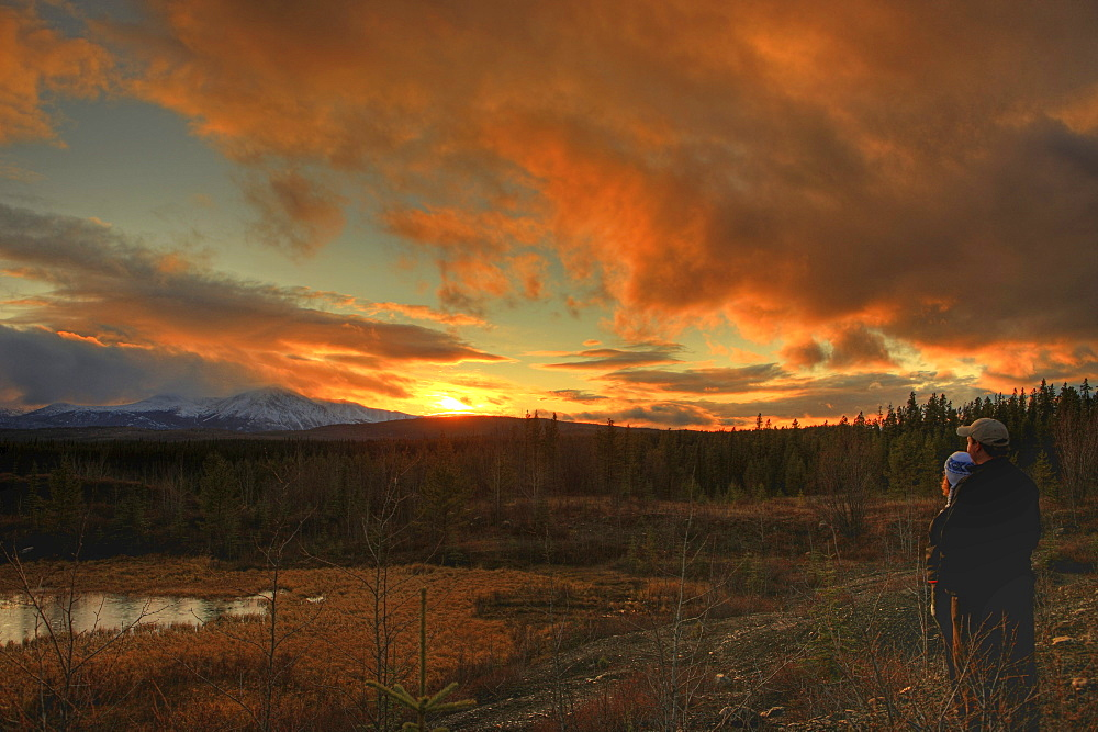 Couple watching sunset over Dawson Peaks, Teslin, Yukon