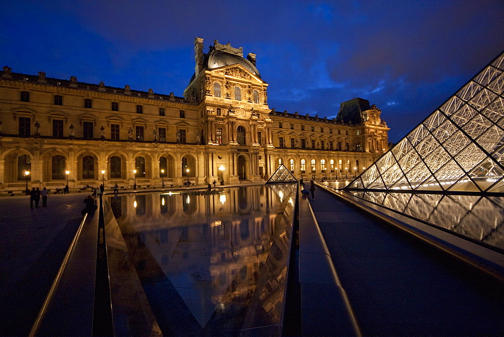 Louvre Pyramid by the architect I.M. Pei and Denon Wing of the Louvre Museum at night, Paris, France