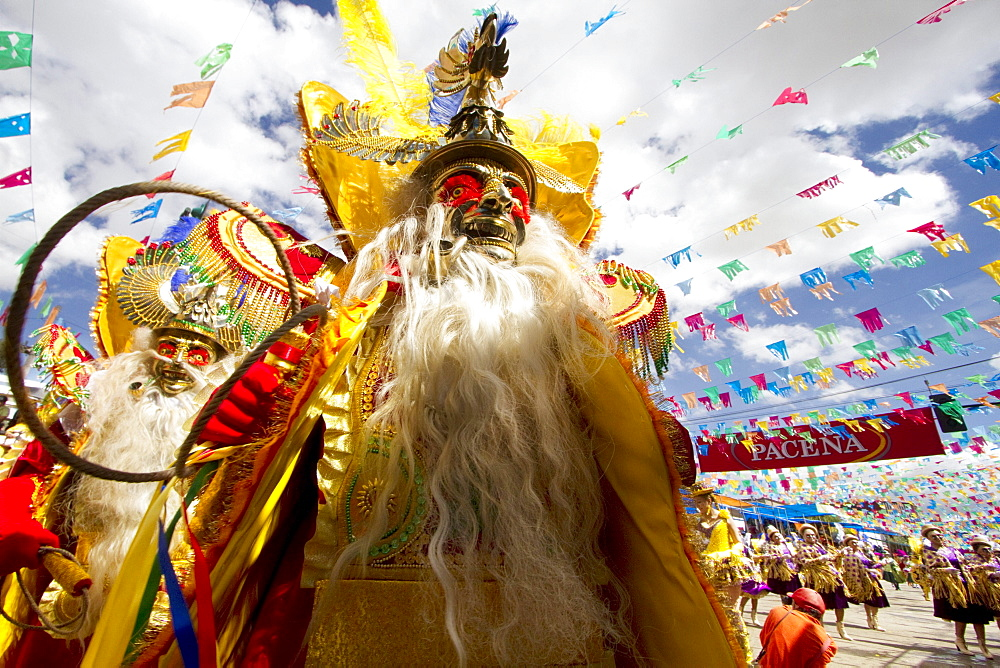 Morenada dancers wearing elaborate masks and costumes in the procession of the Carnaval de Oruro, Oruro, Bolivia