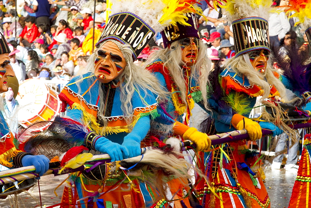 Tobas dancers wearing elaborate masks, feather headdresses and costumes in the procession of the Carnaval de Oruro, Oruro, Bolivia