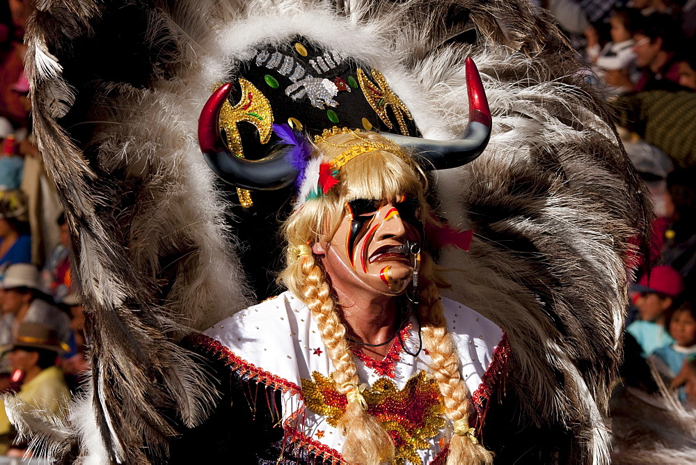 Tobas dancer wearing an elaborate mask, feather headdress and costume in the procession of the Carnaval de Oruro, Oruro, Bolivia