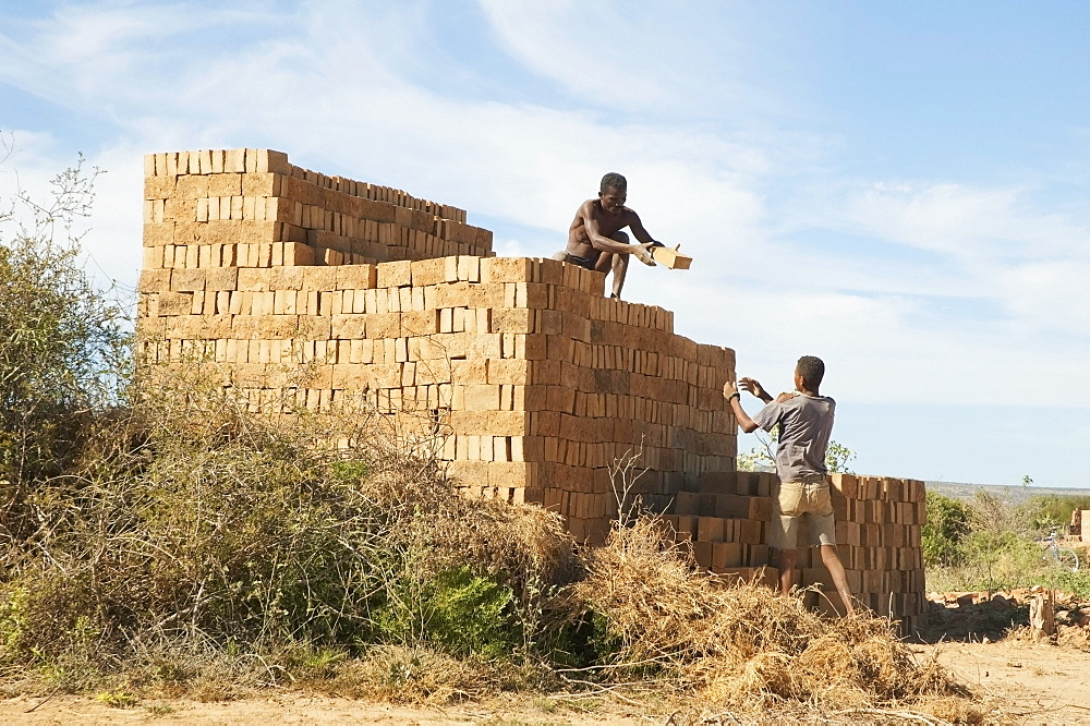 Men piling bricks for firing in Antsokay, Toliara Province, Madagascar