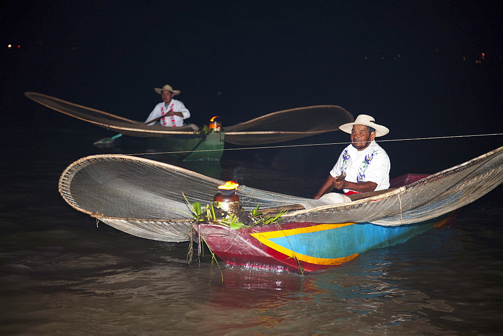 Fishermen with butterfly nets in Lake Pátzcuaro at night, Michoacán, Mexico