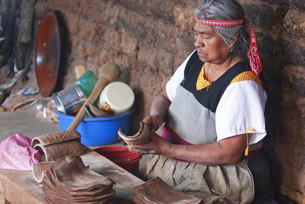 Old Purupecha woman making pottery candle stick holders, Santa Fu de la Laguna, Michoacun, Mexico