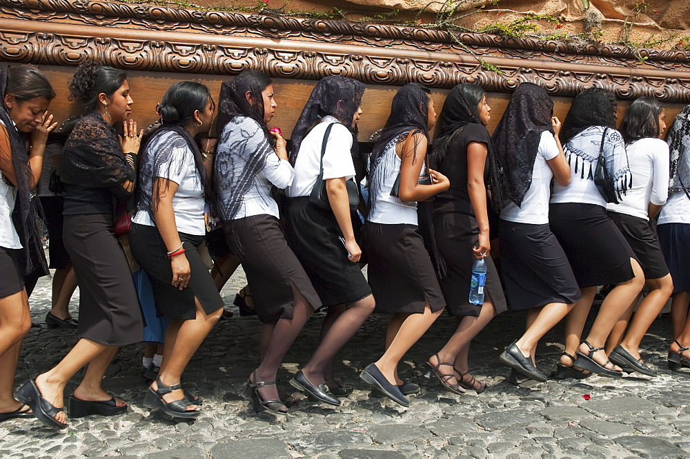 Women dressed in mourning carry the anda (float) of the sorrowful Virgin Mary during a Good Friday Procession in Antigua Guatemala, Sacatepéquez, Guatemala - 1116-27261