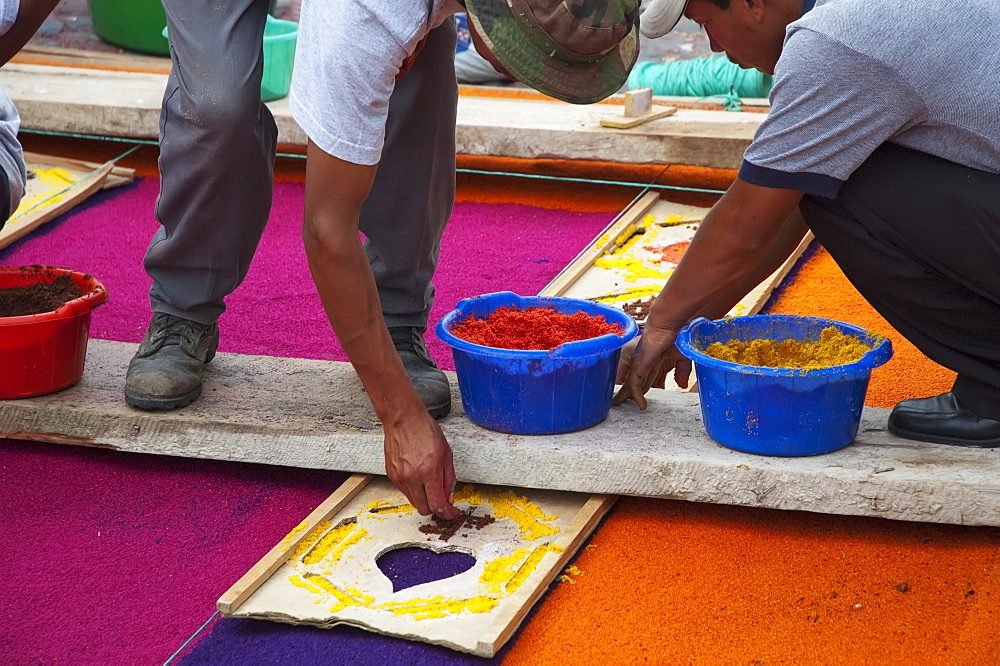 People working on a carpet made of sand & sawdust along the Good Friday processional route. Carpet-making is thought of as a sacrificial act, as the elaborate detail and time that go into the carpet making is a way for people to give something of themselves in memory of the crucifixion of Jesus. These carpets last on average 2 hours before they are destroyed by the many feet that march over them during a procession in Antigua Guatemala., Sacatepuquez, Guatemala