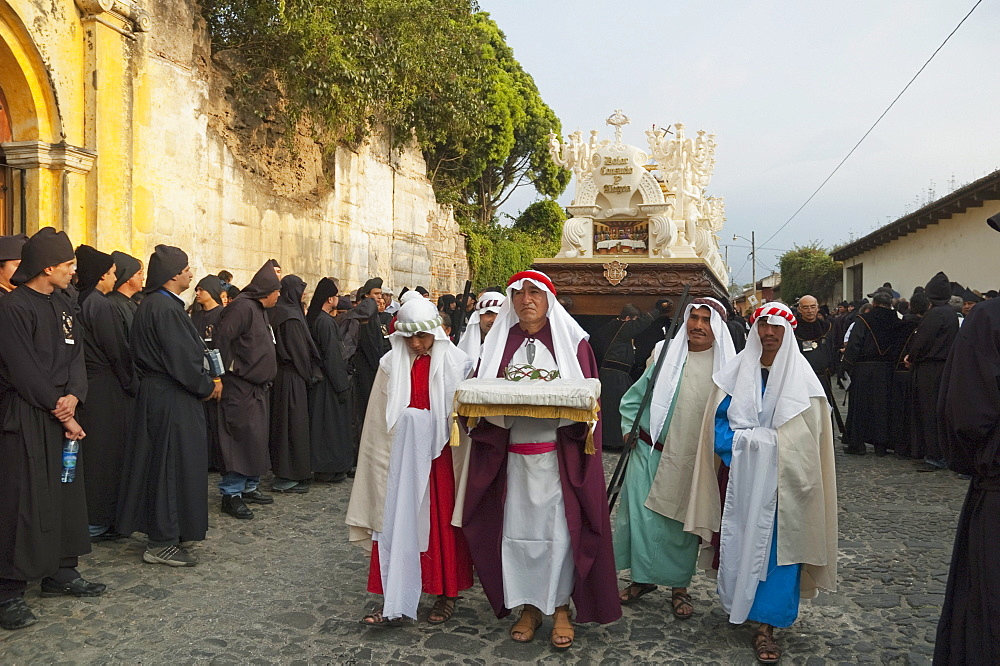 Men dressed in mourning carrying the anda (float) of the Last Supper during the Holy Burial Procession on Good Friday in Antigua Guatemala, Sacatepuquez, Guatemala