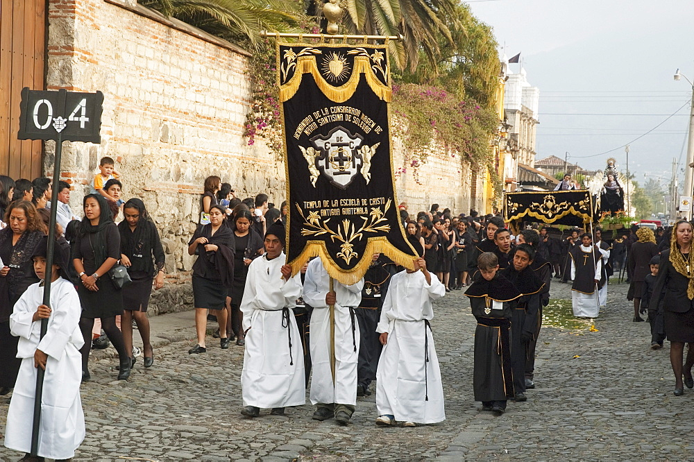 Boys carrying standards in front of the anda (float) of the sorrowful Virgin Mary during the Holy Burial Procession on Good Friday in Antigua Guatemala, Sacatepuquez, Guatemala