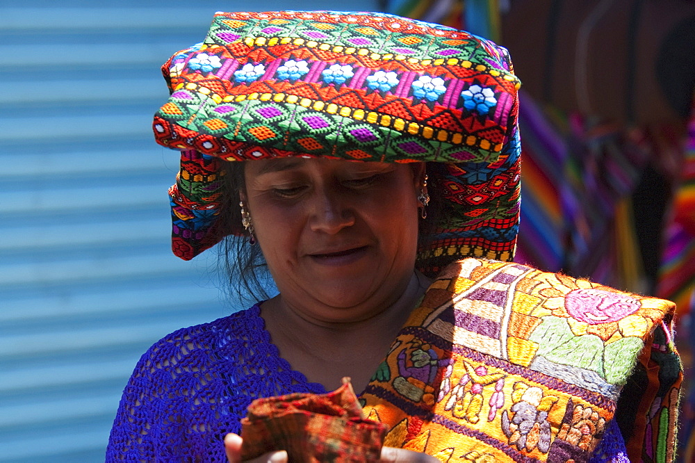 Maya woman selling embroidered table cloths at the Sunday Market in Chichicastenango, El Quichu, Guatemala