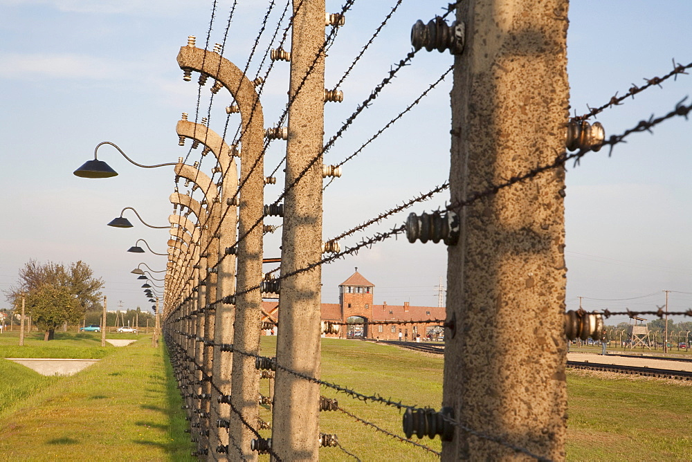 View of the Main Guard House through the electrified barbed wire fence separating sections of the Auschwitz-Birkenau Concentration Camp, Oswiecim, Malopolska, Poland