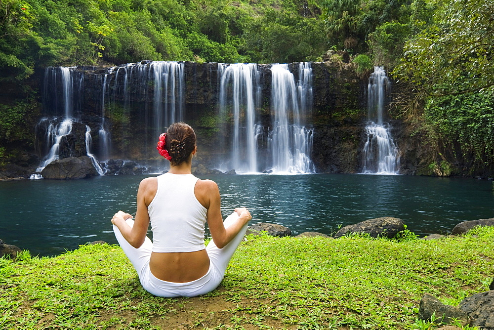 Hawaii, Kauai, Woman sitting near Kilauea Falls, View from behind.
