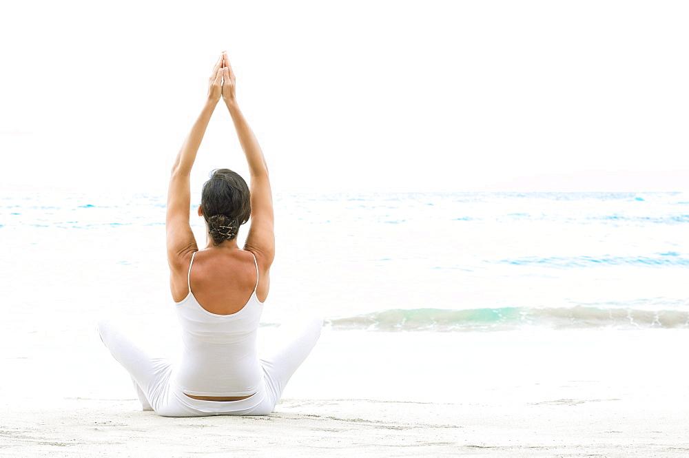 Hawaii, Woman meditating on ocean shore.