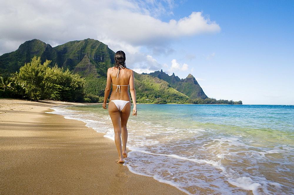 Hawaii, Kauai, Haena Beach Tunnels Beach, Woman walking along sandy shore.