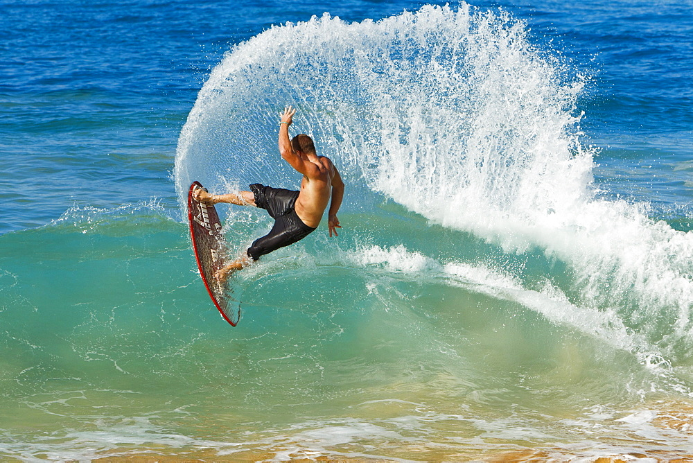 Hawaii, Maui, Makena, Skimboarder carves big turn on wave
