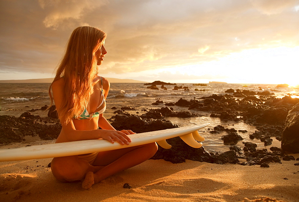 Hawaii, Maui, Makena, Surfer girl sitting on sand at sunset - 1116-27893
