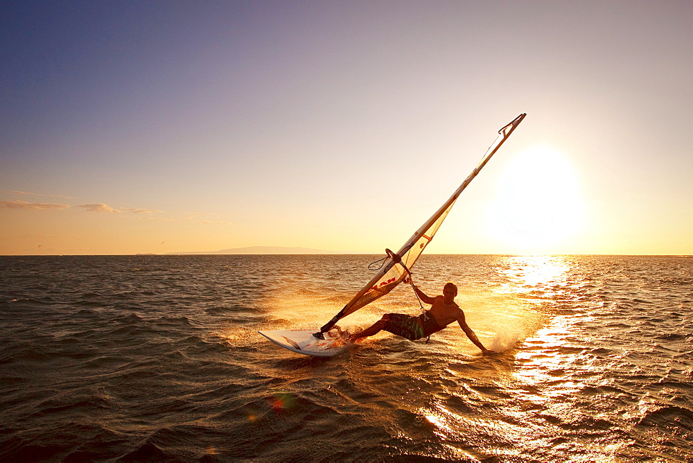Hawaii, Maui, Kihei, Windsurfer sailing off the coast of south Maui at sunset.