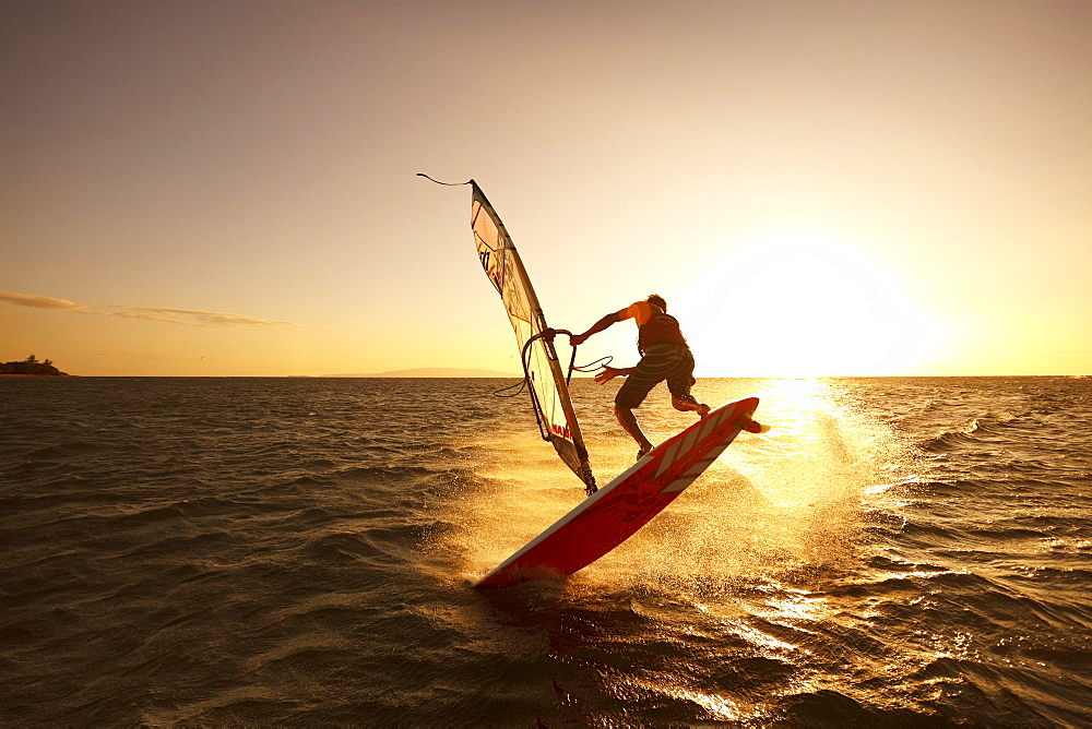 Hawaii, Maui, Kihei, Windsurfer sailing off the coast of south Maui at sunset