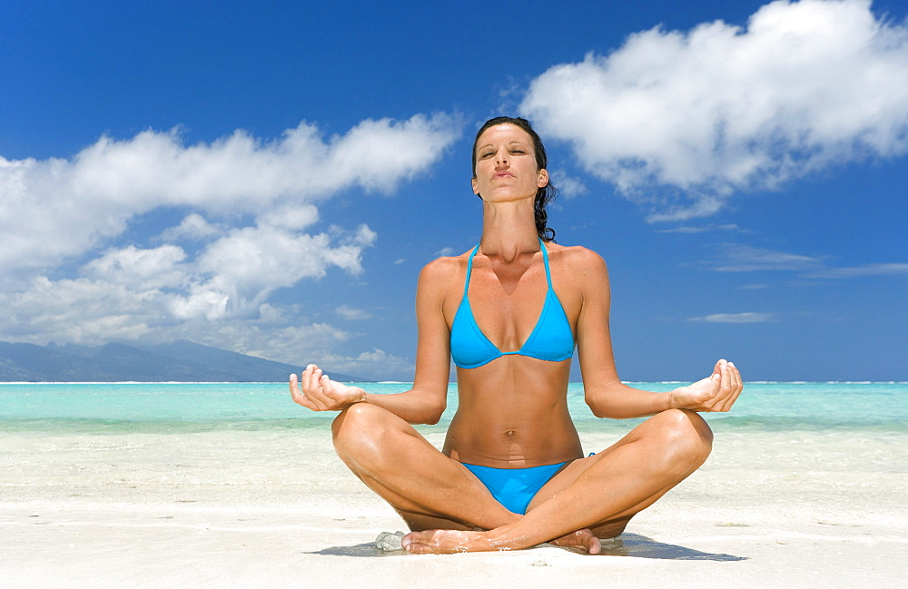 Woman practicing yoga on tropical beach, Lotus position.