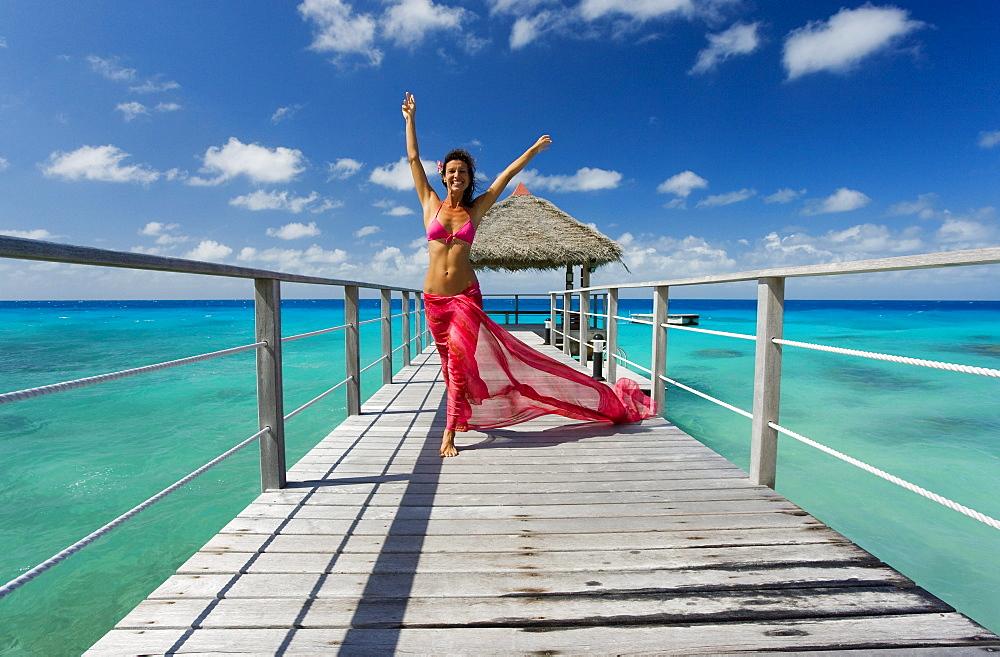 French Polynesia, Tuamotu Islands, Rangiroa Atoll, Woman walking on ocean pier wearing pink pareo.