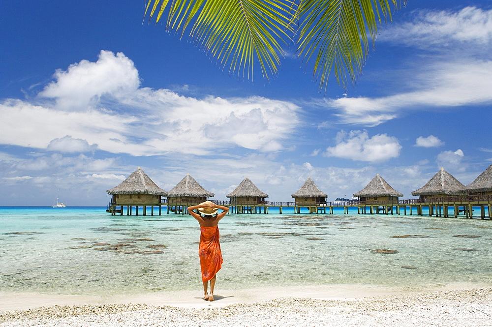 French Polynesia, Tuamotu Islands, Rangiroa Atoll, Woman on beach near luxury resort.