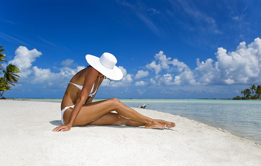 French Polynesia, Tuamotu Islands, Rangiroa Atoll, Woman sitting on white sand beach.