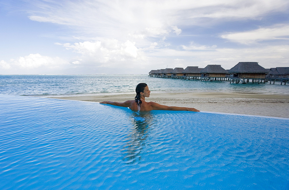 French Polynesia, Moorea, Woman relaxing in resort pool, Luxury resort bungalows in background.