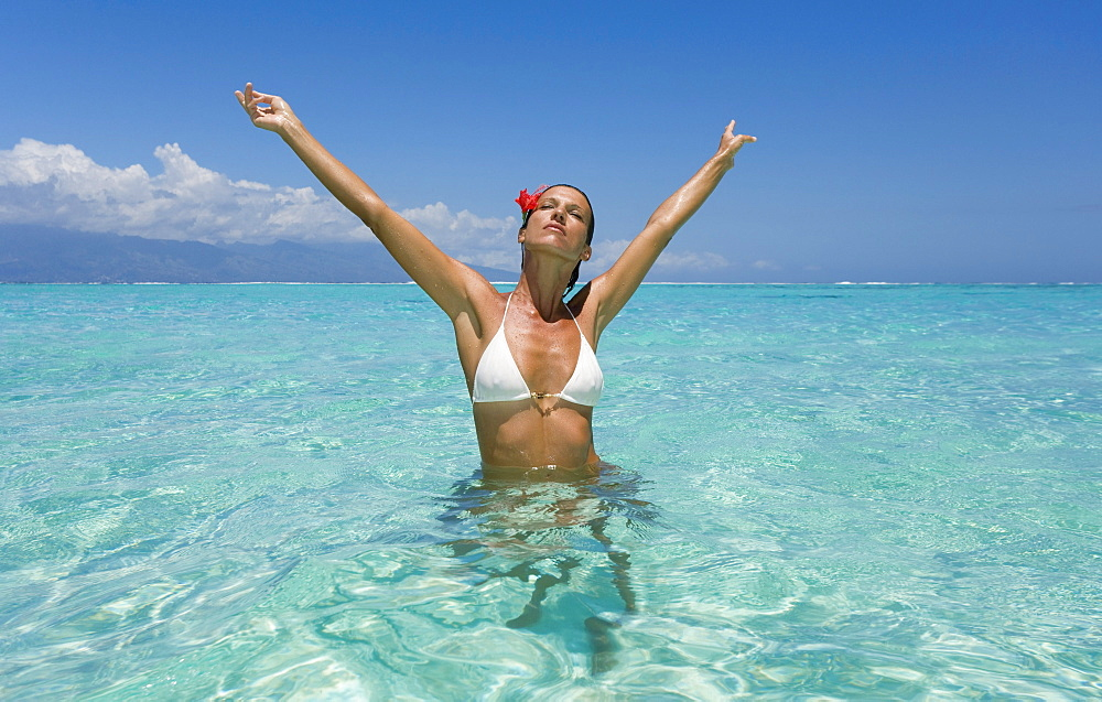 Woman standing in tropical ocean water.
