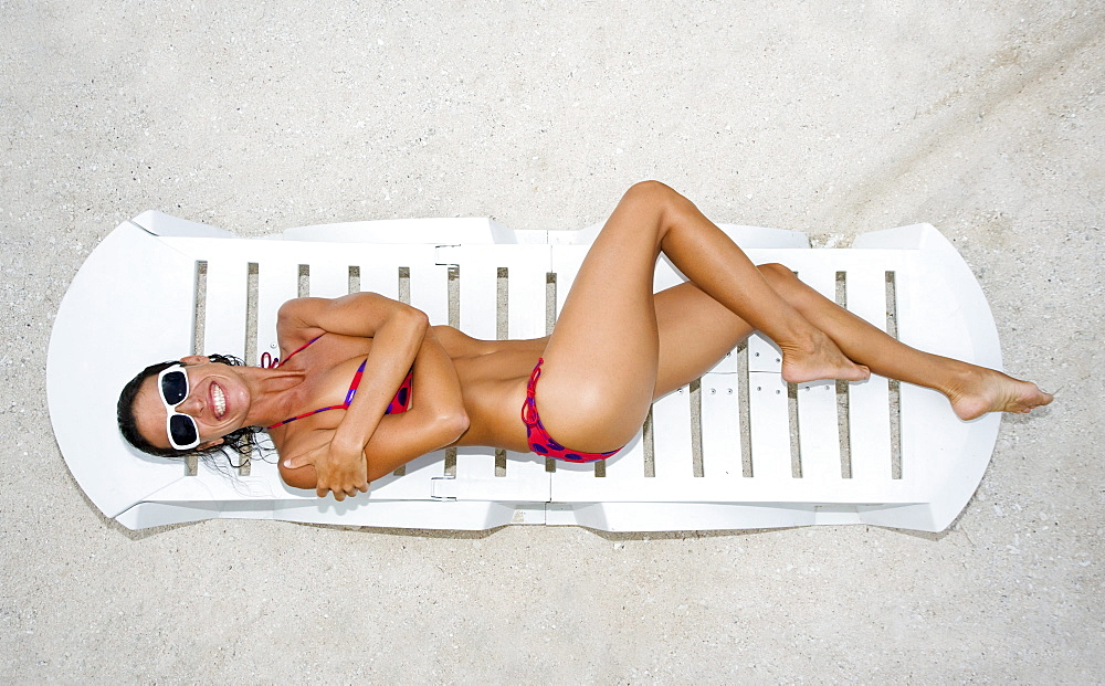Woman lounging on beach chair, White sand beach, View from above.