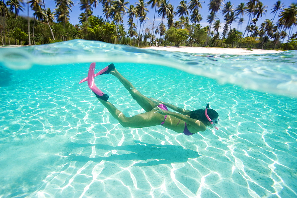 Woman snorkeling in tropical ocean water, Beach in distance, Over/under view.